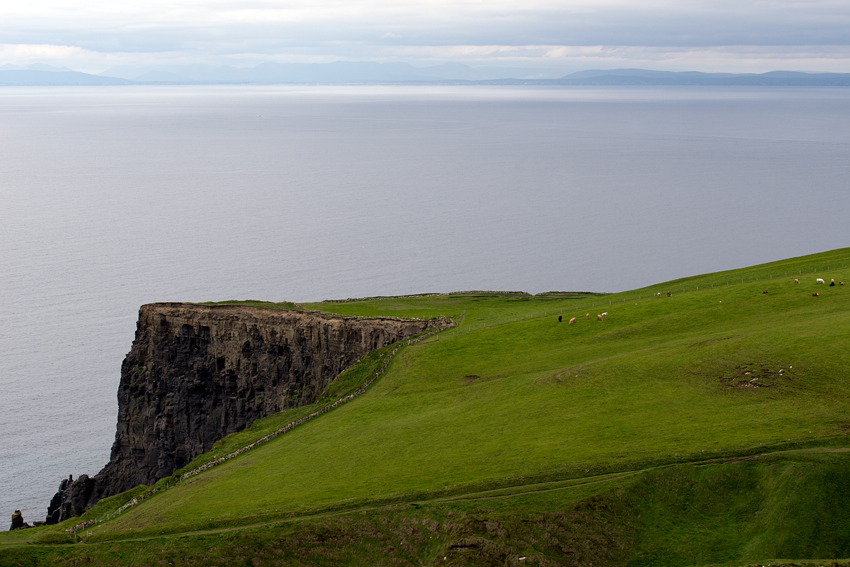 Pastures at the Cliffs of Moher, with the hills of County Galway in the distance.