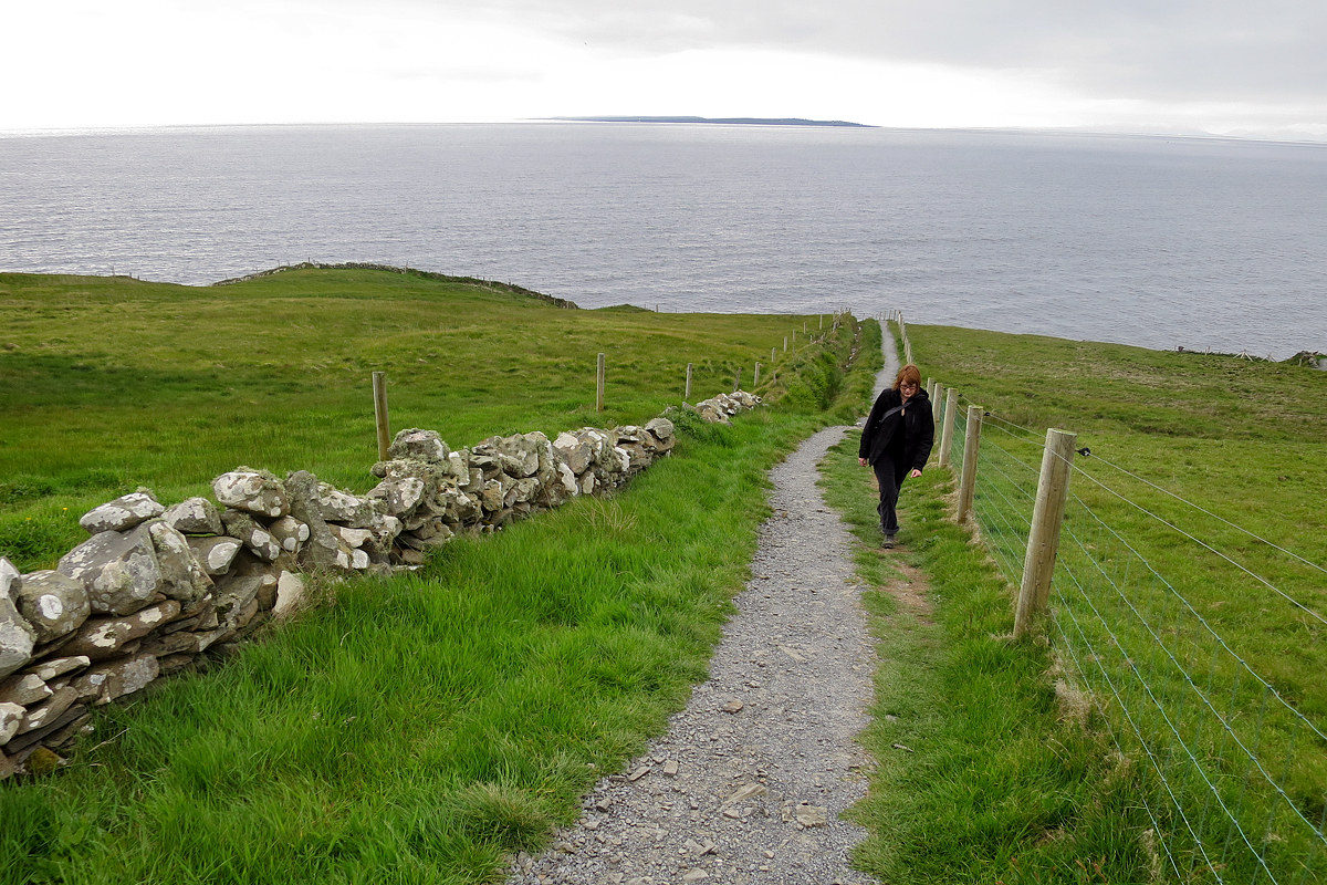 Kris hiking along the coast, with Inisheer (Irish: Inis Oírr) of the Aran Islands in the distance.