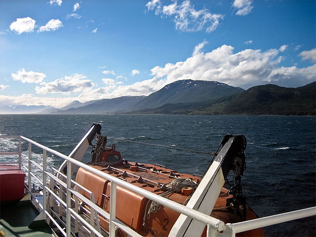 Sailing the Beagle Channel in high summer. The air is cool and fresh, but the late afternoon sun is warm. The twin engines rumble deep within the heart of the ship, and the bow shears away the cold waters as kelp gulls circle above us.