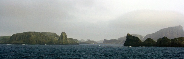 Approaching the South Shetland Islands - hard, jagged rocks like teeth. The air is cold and the sun is a bleary smudge in the gathering clouds. Except for the rumble of the engines, all is silent.